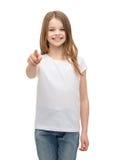 Niña en camiseta blanca en blanco que señala en usted Foto de archivo libre de regalías
