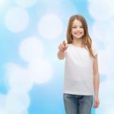 Niña en camiseta blanca en blanco que señala en usted Imágenes de archivo libres de regalías