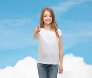 Niña en camiseta blanca en blanco que señala en usted Imagen de archivo libre de regalías