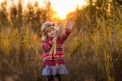 Niña en campo con puesta del sol Fotos de archivo