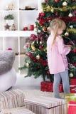Niña en casa que adorna el árbol de navidad Fotos de archivo