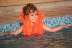 Niña en chaleco inflable en piscina Fotos de archivo