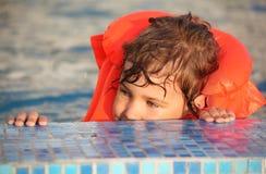 Niña en chaleco inflable en piscina Imagenes de archivo