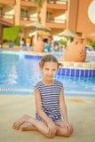 Niña en chaleco rayado cerca de la piscina del centro turístico Fotos de archivo