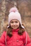 Niña en chaqueta roja brillante y casquillo rosado hecho punto el la primavera fotos de archivo