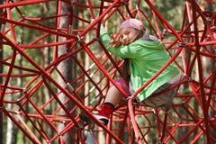 Niña en cuerdas de la gimnasia de la selva Imagen de archivo