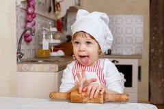 Niña en delantal en la cocina. Imagenes de archivo
