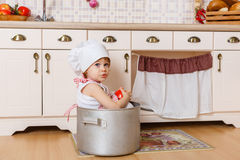 Niña en delantal en la cocina Fotografía de archivo