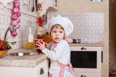Niña en delantal en la cocina Imagenes de archivo