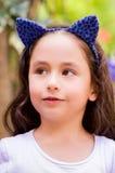 Niña en el aire libre en una naturaleza del verano, accesorios del azul que llevan de un tigre de los oídos sobre su cabeza en un Fotos de archivo