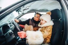 Niña en el coche como un conductor y pequeño muchacho cerca de ella como passanger fotografía de archivo libre de regalías