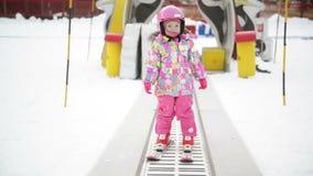 Niña en el equipo del invierno que permanece en Ski Conveyor El niño se está divirtiendo comienza a esquiar Experiencia feliz del almacen de metraje de vídeo
