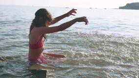 Niña en el mar Adolescente de la muchacha que se baña en niñez y sueños felices del agua del mar Fotos de archivo