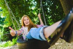 Niña en el patio Niño que juega al aire libre en verano Adolescente en un oscilación Foto de archivo