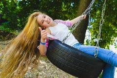 Niña en el patio Niño que juega al aire libre en verano Adolescente en un oscilación Imagen de archivo