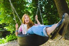 Niña en el patio Niño que juega al aire libre en verano Adolescente en un oscilación Imágenes de archivo libres de regalías