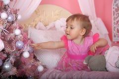 Niña en el rosa que sostiene una bola Foto de archivo