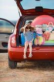 Niña en el sombrero de paja que se sienta en el tronco de un coche Foto de archivo