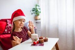Niña en el sombrero de Papá Noel con las galletas del jengibre de la Navidad y la taza de cacao con la melcocha fotografía de archivo libre de regalías