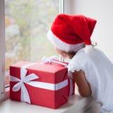 Niña en el sombrero de Papá Noel que mira fuera de ventana al lado de las cajas con los presentes Foto de archivo
