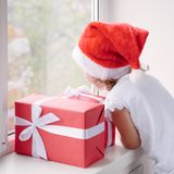 Niña en el sombrero de Papá Noel que mira fuera de ventana al lado de ingenio de las cajas Imagen de archivo