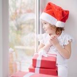 Niña en el sombrero de Papá Noel que se sienta por la ventana con la caja de Chris Imágenes de archivo libres de regalías