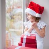 Niña en el sombrero de Papá Noel que se sienta por la ventana con la caja de regalos de la Navidad Imagen de archivo