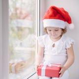 Niña en el sombrero de Papá Noel que se sienta por la ventana y que sostiene la caja w Foto de archivo libre de regalías