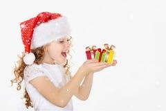 Niña en el sombrero de Papá Noel, regalo de la Navidad del control en su mano fotos de archivo libres de regalías