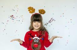 Niña en el sombrero de Rudolf que espera una Navidad en el fondo blanco imagen de archivo
