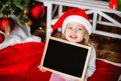Niña en el sombrero de Santa Claus con los tableros Imagen de archivo