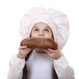 Niña en el sombrero del cocinero que mira para arriba Imagenes de archivo