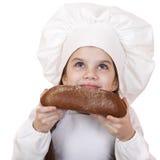 Niña en el sombrero del cocinero que mira para arriba Imagen de archivo