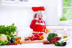 Niña en el sombrero del cocinero que prepara el almuerzo Imagenes de archivo