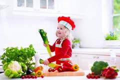 Niña en el sombrero del cocinero que prepara el almuerzo Imagen de archivo libre de regalías