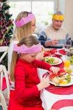 Niña en el sombrero del partido que sostiene las galletas de la Navidad Imagenes de archivo
