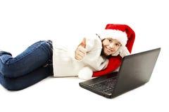 Niña en el sombrero rojo de Papá Noel con el ordenador portátil Fotos de archivo libres de regalías