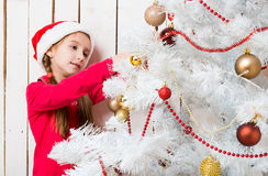 Niña en el sombrero rojo de santa que adorna el árbol del Año Nuevo Fotografía de archivo libre de regalías