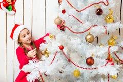 Niña en el sombrero rojo de santa que adorna el árbol del Año Nuevo Foto de archivo