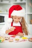 Niña en el tiempo de la Navidad en la cocina Imágenes de archivo libres de regalías