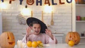 Niña en el traje asustadizo de la bruja que salta de debajo la tabla, partido de Halloween metrajes