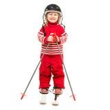 Niña en el traje de esquí rojo que se coloca en los esquís Fotos de archivo libres de regalías