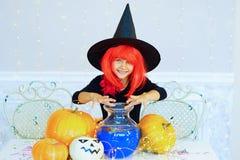Niña en el traje de la bruja que juega con las calabazas Fotografía de archivo