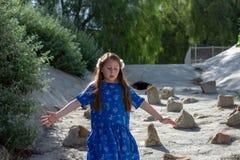 Niña en el vestido azul que juega en dren de la tormenta en el parque por las piedras fotografía de archivo libre de regalías
