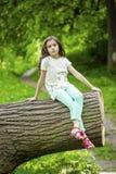 Niña en el vestido blanco que se sienta en tronco de árbol sobre gras verdes Imagen de archivo