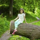 Niña en el vestido blanco que se sienta en tronco de árbol sobre gras verdes Imágenes de archivo libres de regalías