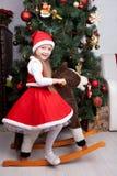 Niña en el vestido de la Navidad que juega con el caballo del juguete Fotografía de archivo libre de regalías