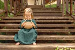 niña en el vestido de lino retro del vintage descalzo sentando en las escaleras de madera en el parque que mira en cesta de mimbr Fotos de archivo libres de regalías