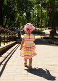Niña en el vestido hermoso que corre lejos en el camino en el parque Fotos de archivo libres de regalías
