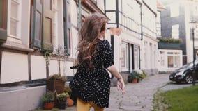 Niña en el vestido negro que corre en el camino viejo Cámara lenta de la visión trasera Casas Half-timbered Niñez despreocupada f metrajes